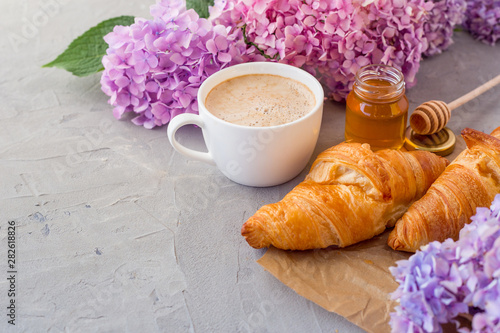 Breakfast served with coffee, croissants, natural honey jar and flowers on gray stone background Fototapeta