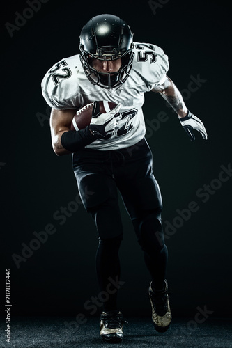 Canvas Print American football sportsman player in helmet isolated run in action on black background