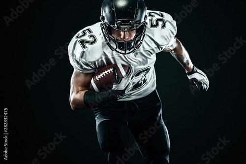 Tablou Canvas American football sportsman player in helmet isolated run in action on black background