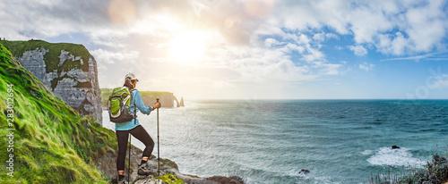 Fotografiet Frau mit Rucksack beim Wandern an den Falaises von Etretat