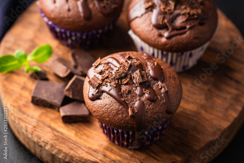 Carta da parati Double chocolate muffins covered with melted chocolate on a wooden background