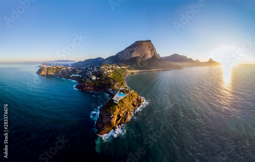 Panoramic view of the coastline and beach of Joatinga in Rio de Janeiro with its beautiful picturesque natural richness and far in the background the well known landmark peaks of the city