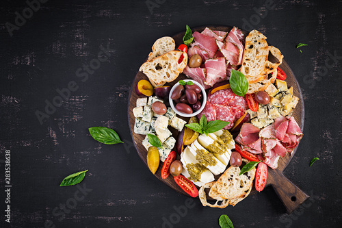 Antipasto platter with ham, prosciutto, salami, blue cheese, mozzarella with pesto and olives on a wooden background Fototapeta