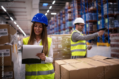 Fotografiet Female factory worker in reflective uniform with hardhat helmet checking new arrival of goods in warehouse while worker using bar code reader in background