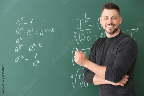 Fototapeta Handsome math teacher writing on blackboard in classroom