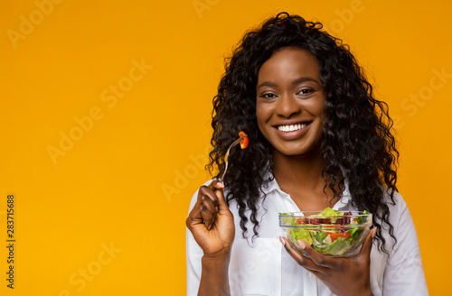 Photo Happy african american woman eating vegetable salad