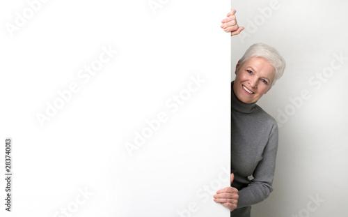 Fotomural Beautiful senior woman hiding behind big white empty board