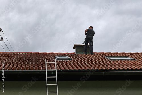 Foto Ein Kaminkehrer auf dem Dach säubert mit der Bürste einen Kamin
