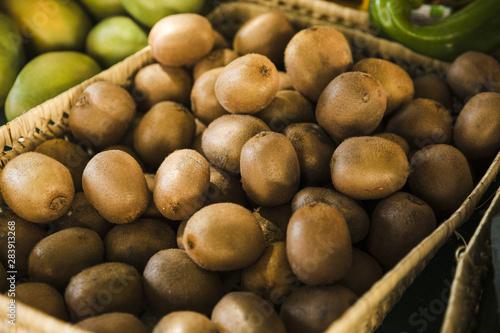 Fotografie, Obraz Exotic delicious organic kiwi in wicker basket at market