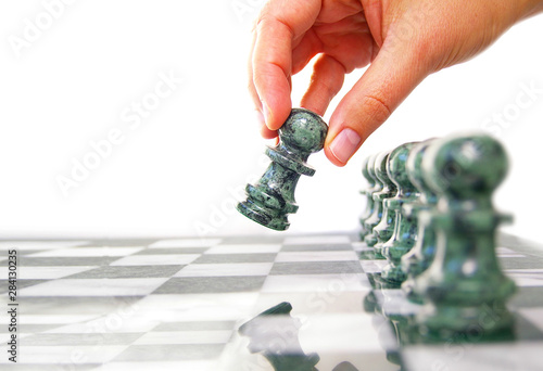 Fotografia, Obraz Woman moving a chess piece ahead