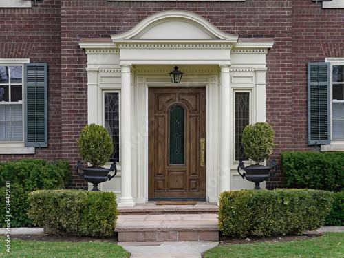 Fotografija elegant wooden front door with portico and shrubbery