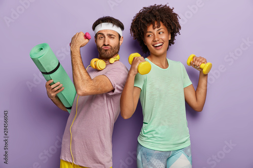 Obraz na plátně Glad multiethnic husband and wife attend sport center, exercise with dumbbells,