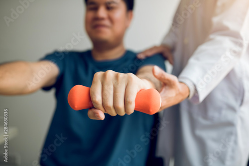 Foto Asian physiotherapist helping a patient lifting dumbbells work through his recovery with weights in clinic room