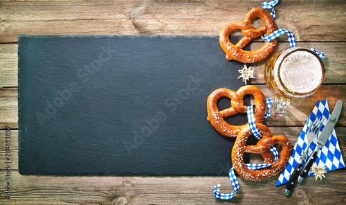 Fotografiet Bavarian pretzels with silverware and beer stein on wooden table.
