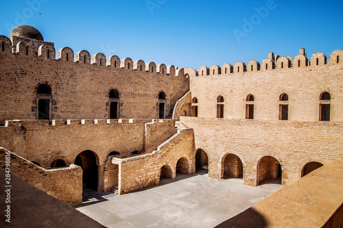 Slika na platnu The stone walls, stairs and passages of Ribat Sousse, in the rays of the hot African sun