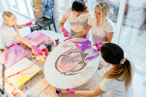 Creative woman painter teach group of four female students creating fluid acrylic abstract painting in art therapy class, with table full of bottle with defferent paint colors Fototapete