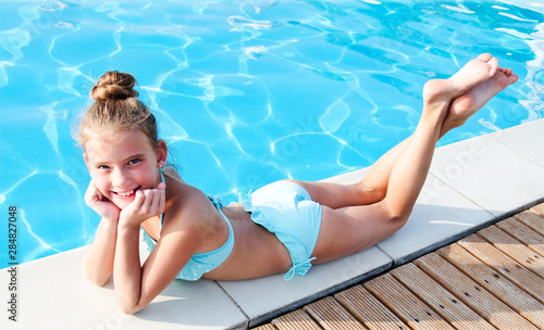 Photo Cute smiling little girl child lying near swimming pool and having fun