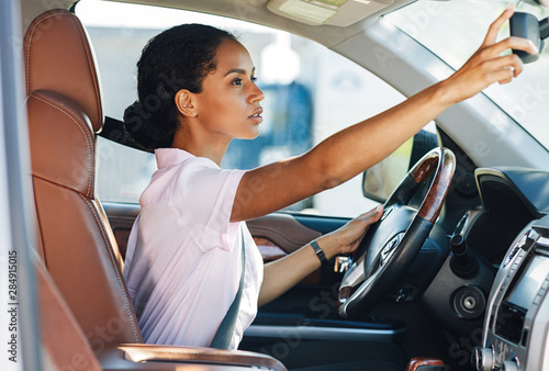 Carta da parati Side view of woman adjusting rear view mirror while driving a car