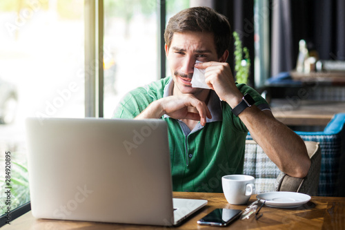 Young sad businessman in green t-shirt sitting, crying and cleaning his tears with tissue napin and looking with upset face Fototapete
