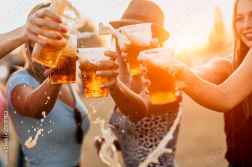 Fotografia Female friends cheering with beer at music festival