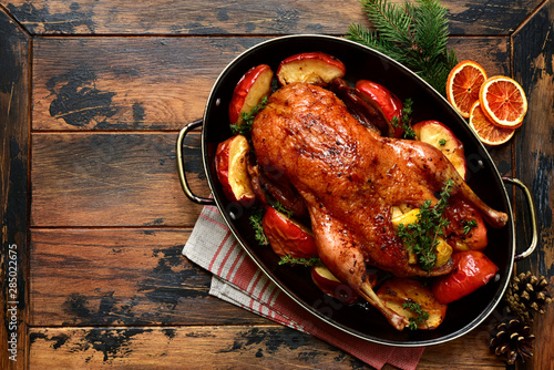 Fotografia Roast goose stuffed with baked apples in a skillet, festive christmas recipe