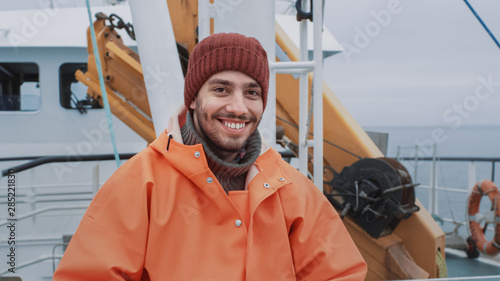 Obraz na płótnie Portrait of Dressed in Bright Protective Coat Smiling on Camera Fisherman on Commercial Fishing Boat