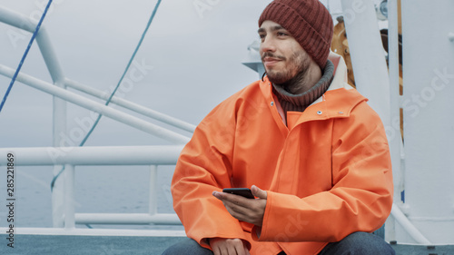 Fotografia Casualy Dressed Fisherman Using Mobile Phone while Traveling on Ship