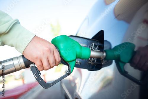 Carta da parati Man filling gasoline fuel in car holding pump