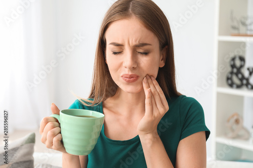 Canvas Print Young woman with sensitive teeth and cup of hot coffee at home