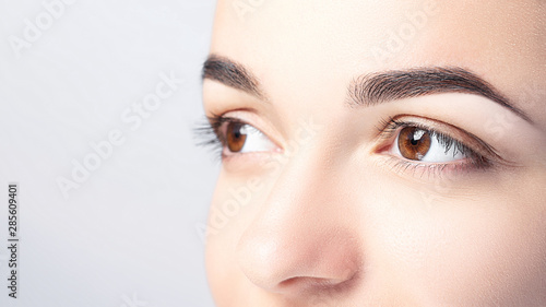 Fotografija Woman with beautiful eyebrows close-up on a light background with copy space
