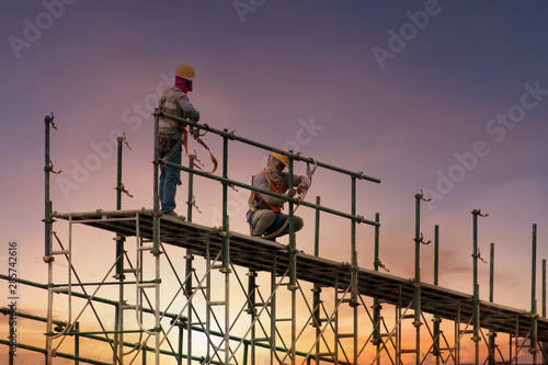 Photo Man working on construction site with scaffold and building with sunset backgrou