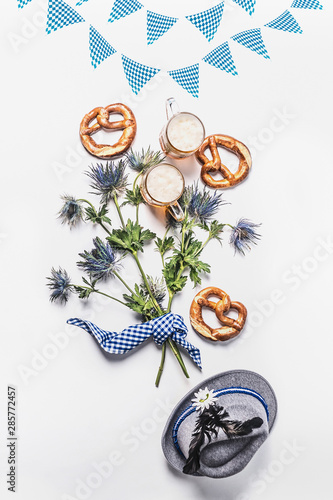 Foto Oktoberfest composition with traditional Bavarian white blue fabric , decoration, pretzel , cups of draft beer, Bavarian hat and bunch of alpine flowers on white background