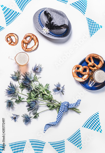Fényképezés Modern Oktoberfest background with traditional Bavarian white blue fabric , decoration, pretzel , cups of draft beer, Bavarian hat and bunch of alpine flowers