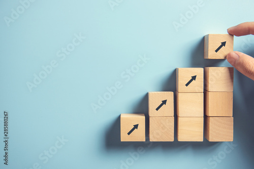 Carta da parati Business concept growth success process, Close up Woman hand arranging wood block stacking as step stair on paper blue background, copy space