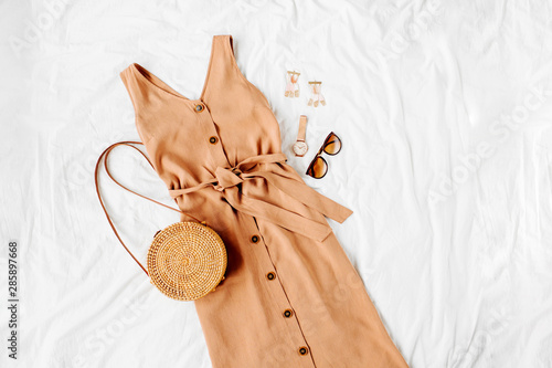 Beige dress with bamboo bag and accessories on white bed Fototapet