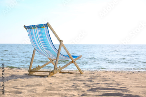 Photo Empty cozy lounger on sand near sea, space for text