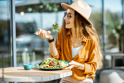 Valokuva Stylish young woman eating healthy salad on a restaurant terrace, feeling happy