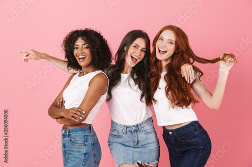 Photo Cheery young three multiethnic girls friends posing isolated over pink wall background