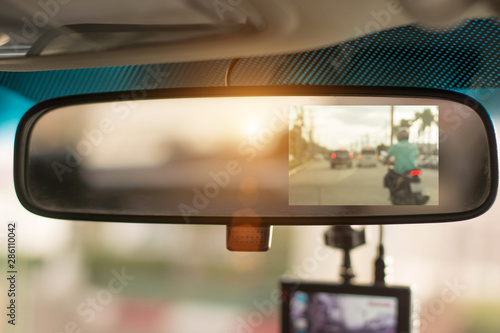 Fotografia Close up car on highway at sunset, with video recorder next to a rear view mirror,video recorder driving a car on highway,car video recorder,Full HD camera recorder for vehicle