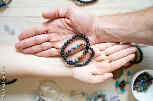 Fotomural High angle view on male and female hands holding crystal gems bracelets handmade