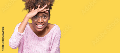 Fotografia, Obraz Beautiful young african american woman wearing glasses over isolated background very happy and smiling looking far away with hand over head