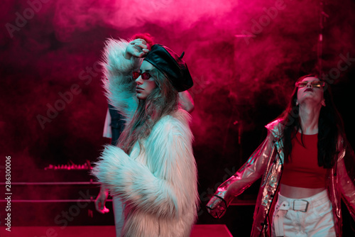 Canvas Print girls dancing in nightclub with neon pink smoke