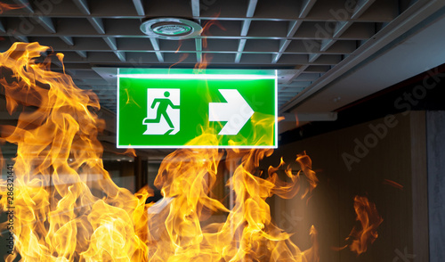 Canvas Print Green fire escape sign hang on the ceiling in the office.