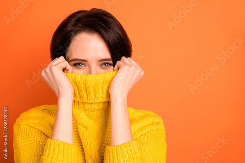 Close up photo of cute nice charming girl hiding from cold by wrapping up in collar while isolated with orange background