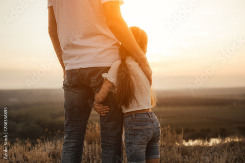 Fototapeta Happy father and daughter hugging while standing at countryside