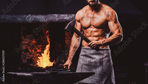 Fotografía Powerful bearded blacksmith with naked torso and protective apron is standing near working stove with hammer in his hand