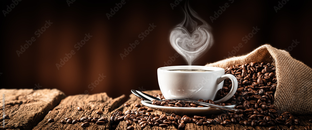White Cup Of Hot Coffee With Heart Shaped Steam On Old Weathered Table With Burlap Sack And Beans