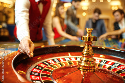 Photo The croupier holds a roulette ball in a casino in his hand.