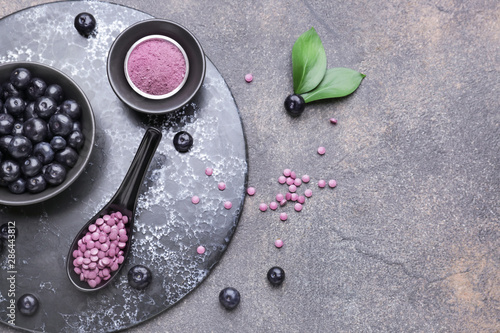 Canvas Print Acai berries with powder and tablets on grey background