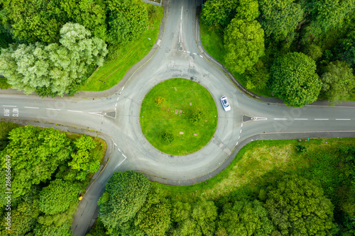 Top down aerial drone view of a small traffic roundabout on a quiet road